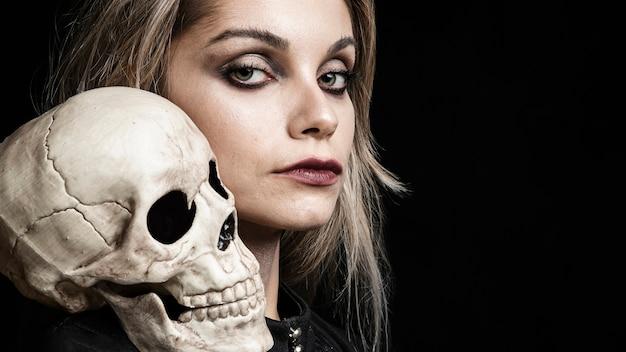 Vista lateral de mujer con cráneo en hombro