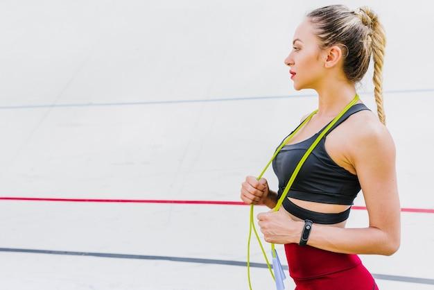 Vista lateral de mujer con cuerda de saltar.