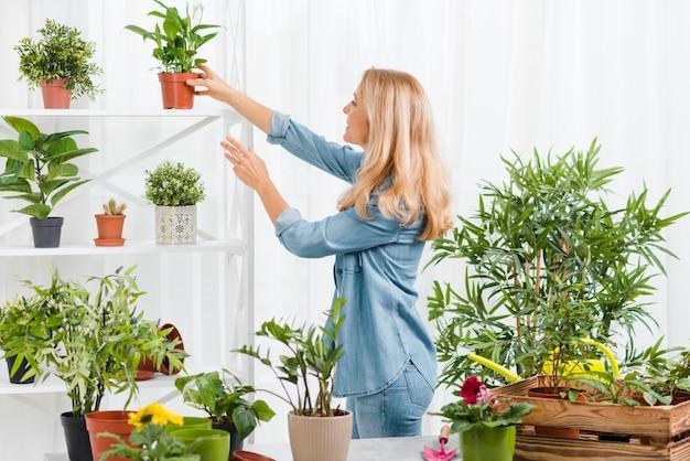 Vista lateral mujer cuidando flores