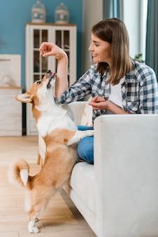 Vista lateral de la mujer dando un regalo a su perro