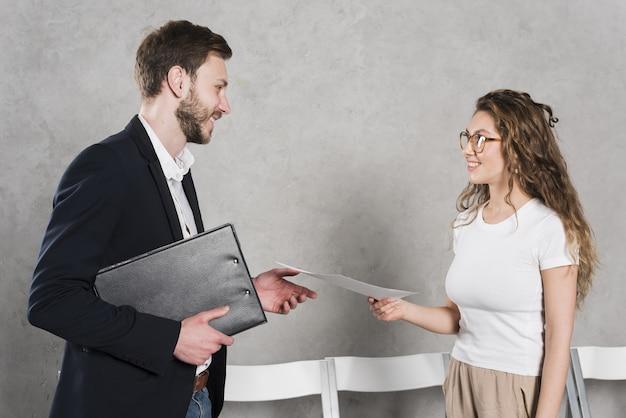 Vista lateral de la mujer dando su currículum al hombre de recursos humanos