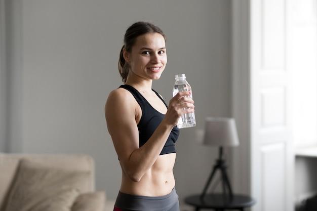 Vista lateral de la mujer deportiva que sostiene la botella de agua