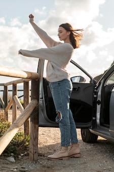 Vista lateral de la mujer disfrutando de la brisa de la playa junto al coche