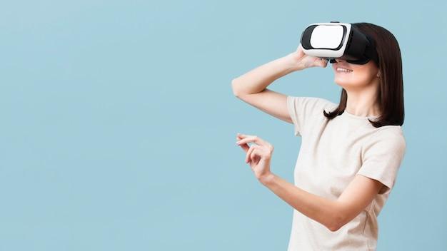 Vista lateral de mujer disfrutando de casco de realidad virtual