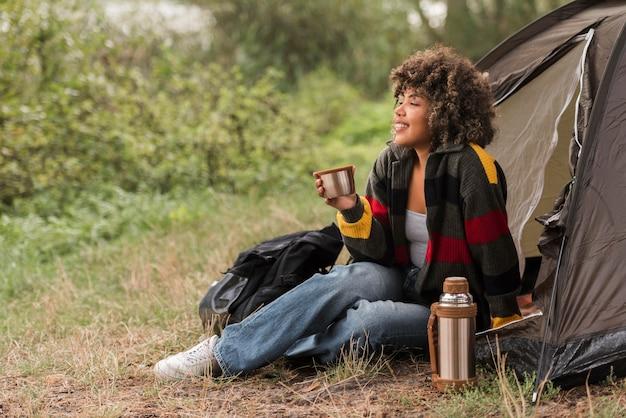 Vista lateral de la mujer disfrutando de la vista mientras acampa al aire libre