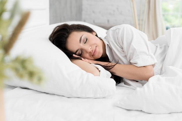 Vista lateral de la mujer durmiendo en la cama