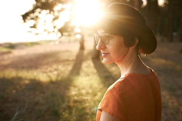 Vista lateral de una mujer elegante y pensativa con el pelo corto que camina al aire libre, con gafas y sombrero, disfrutando de una agradable velada con rayos de luz solar a través de las hojas de los árboles.