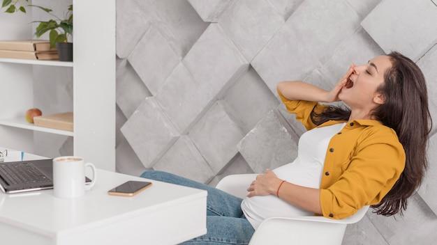 Vista lateral de la mujer embarazada bostezando en casa con ordenador portátil y smartphone