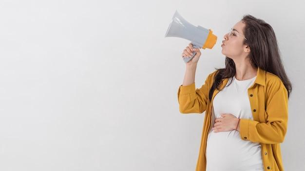 Vista lateral de la mujer embarazada hablando por megáfono