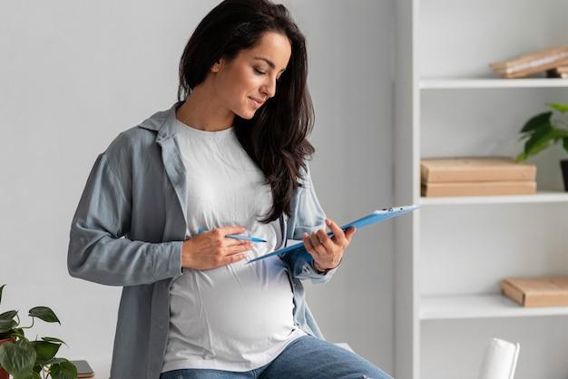 Vista lateral de la mujer embarazada que trabaja desde casa con portapapeles