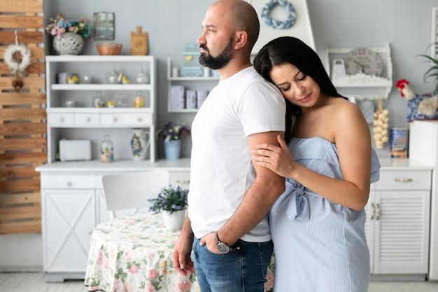 Vista lateral mujer embarazada sosteniendo el brazo de su marido