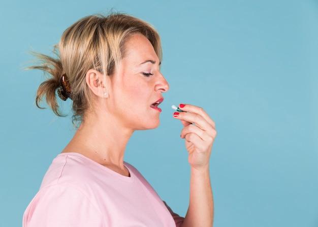 Vista lateral de una mujer enferma tomando cápsulas de vitaminas.