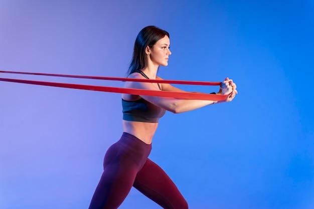 Vista lateral mujer entrenamiento con banda elástica