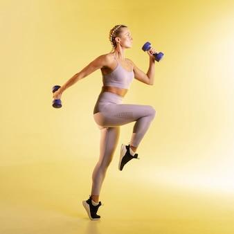 Vista lateral mujer entrenando con pesas