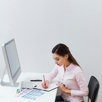 Vista lateral de la mujer escribiendo algo mientras está en el escritorio