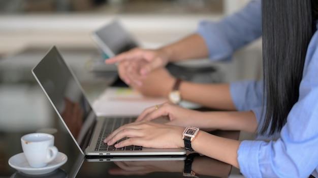 Vista lateral de la mujer escribiendo en la computadora portátil mientras su compañero de trabajo informa sobre su proyecto