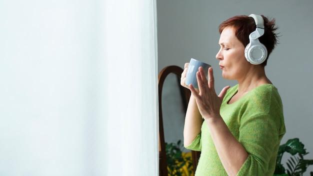 Vista lateral mujer escuchando música y sosteniendo una taza