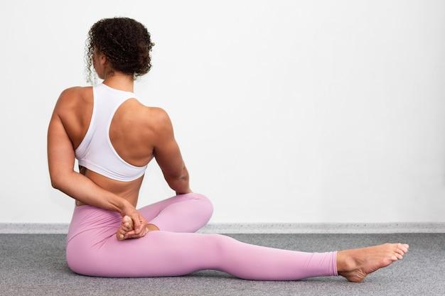 Vista lateral mujer estirando su espalda