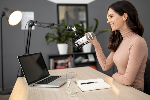 Vista lateral de la mujer en un estudio de radio con laptop y micrófono