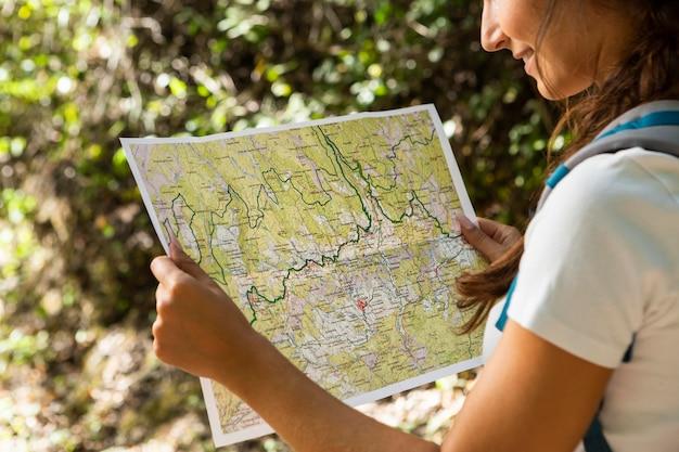 Vista lateral de la mujer explorando la naturaleza mientras mira el mapa