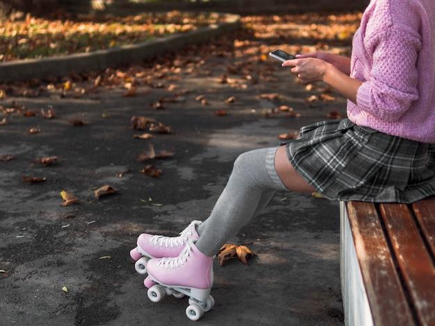 Vista lateral de la mujer en falda con patines y espacio de copia