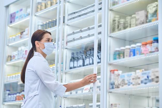 Vista lateral de una mujer farmacéutica abriendo la puerta corrediza de vidrio de la vitrina de la farmacia