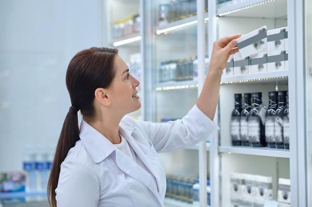 Vista lateral de una mujer farmacéutica complacida tomando una caja de cartón con medicamentos fuera de la estantería