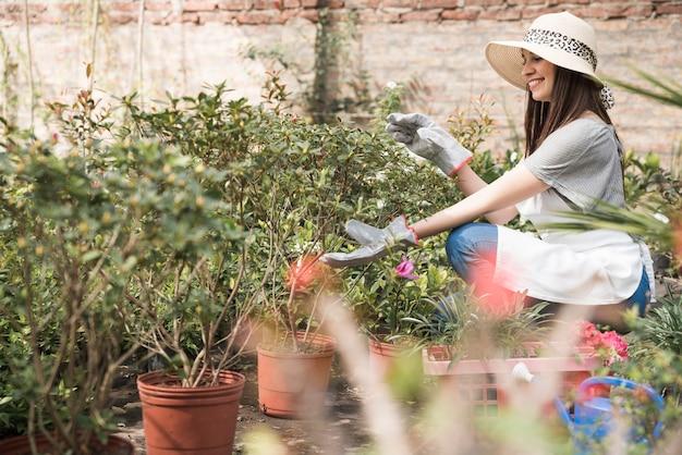 Vista lateral de una mujer feliz examinando plantas en invernadero