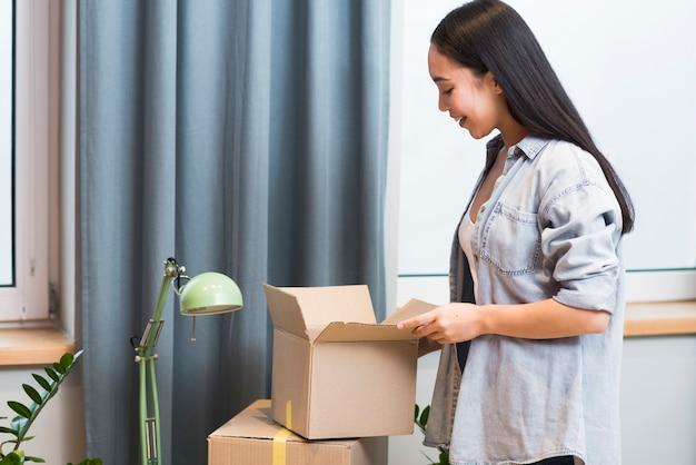 Vista lateral de una mujer feliz con la llegada de pedidos en línea