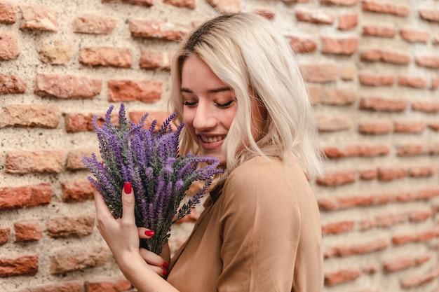 Vista lateral de la mujer feliz con ramo de lavanda