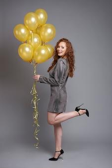 Vista lateral de la mujer feliz sosteniendo un montón de globos