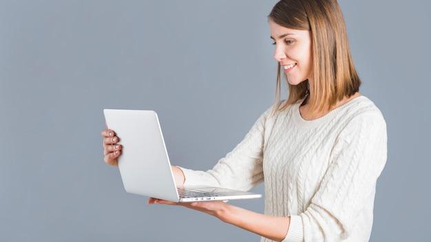 Vista lateral de una mujer feliz sosteniendo portátil sobre fondo gris