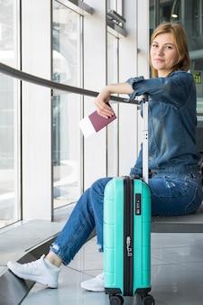 Vista lateral de la mujer frente a la cámara en el aeropuerto