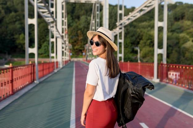 Vista lateral de la mujer con gafas de sol y sombrero posando mientras viaja solo
