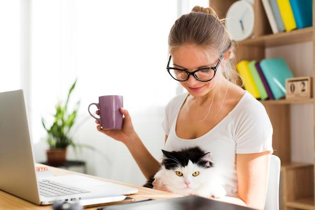 Vista lateral de mujer con gato en el escritorio trabajando desde casa