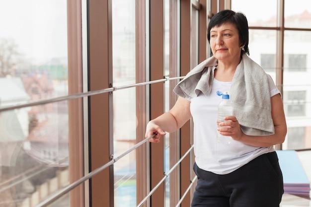 Vista lateral mujer en el gimnasio hidratante