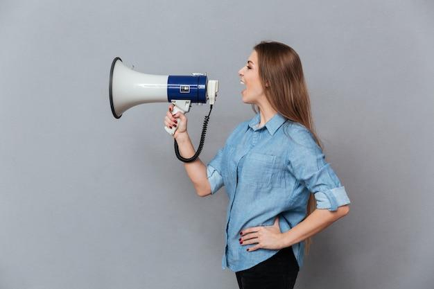 Vista lateral de la mujer gritando en megáfono
