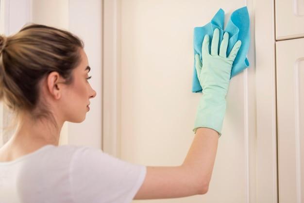 Vista lateral de la mujer con guantes de limpieza de superficie con tela