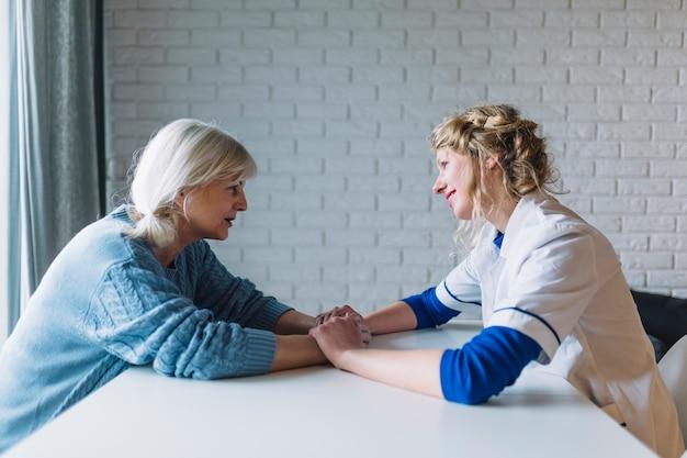 Vista lateral de mujer hablando con enfermera en asilo de ancianos
