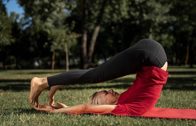 Vista lateral, de, mujer, hacer, yoga, posición, aire libre