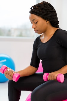 Vista lateral mujer haciendo ejercicio con pesas