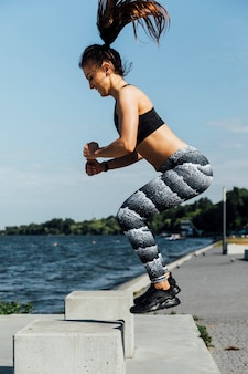 Vista lateral de la mujer haciendo saltos