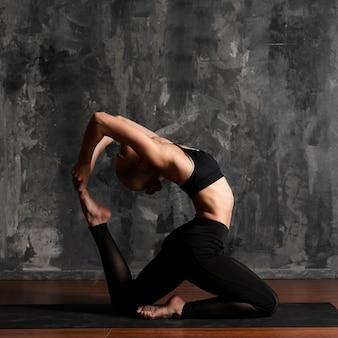 Vista lateral mujer haciendo yoga con fondo de estuco