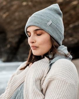 Vista lateral, de, mujer hermosa, posar, en la playa