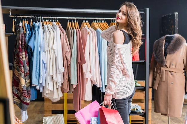 Vista lateral de la mujer hermosa que sostiene el bolso de compras en tienda
