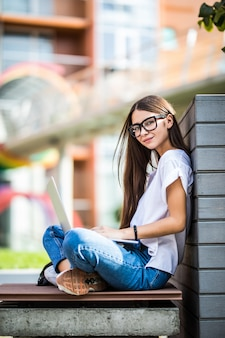 Vista lateral de una mujer joven en anteojos sentado en el banco en el parque y usando la computadora portátil