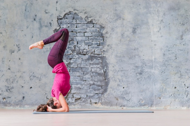 Vista lateral de una mujer joven de la aptitud que se coloca en su cabeza que hace yoga