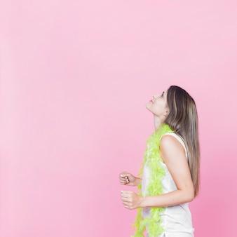 Vista lateral de una mujer joven bailando sobre fondo rosa