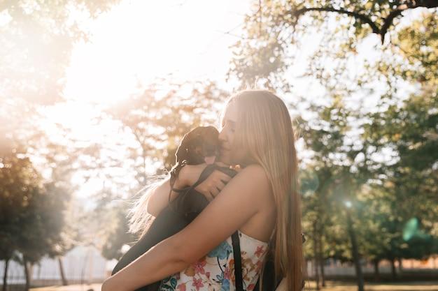 Vista lateral de una mujer joven besando a su perro en el jardín