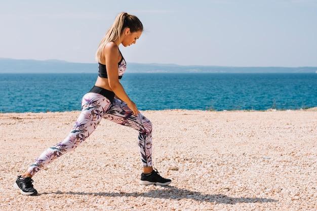 Vista lateral, de, un, mujer joven, ejercitar, cerca, el, playa